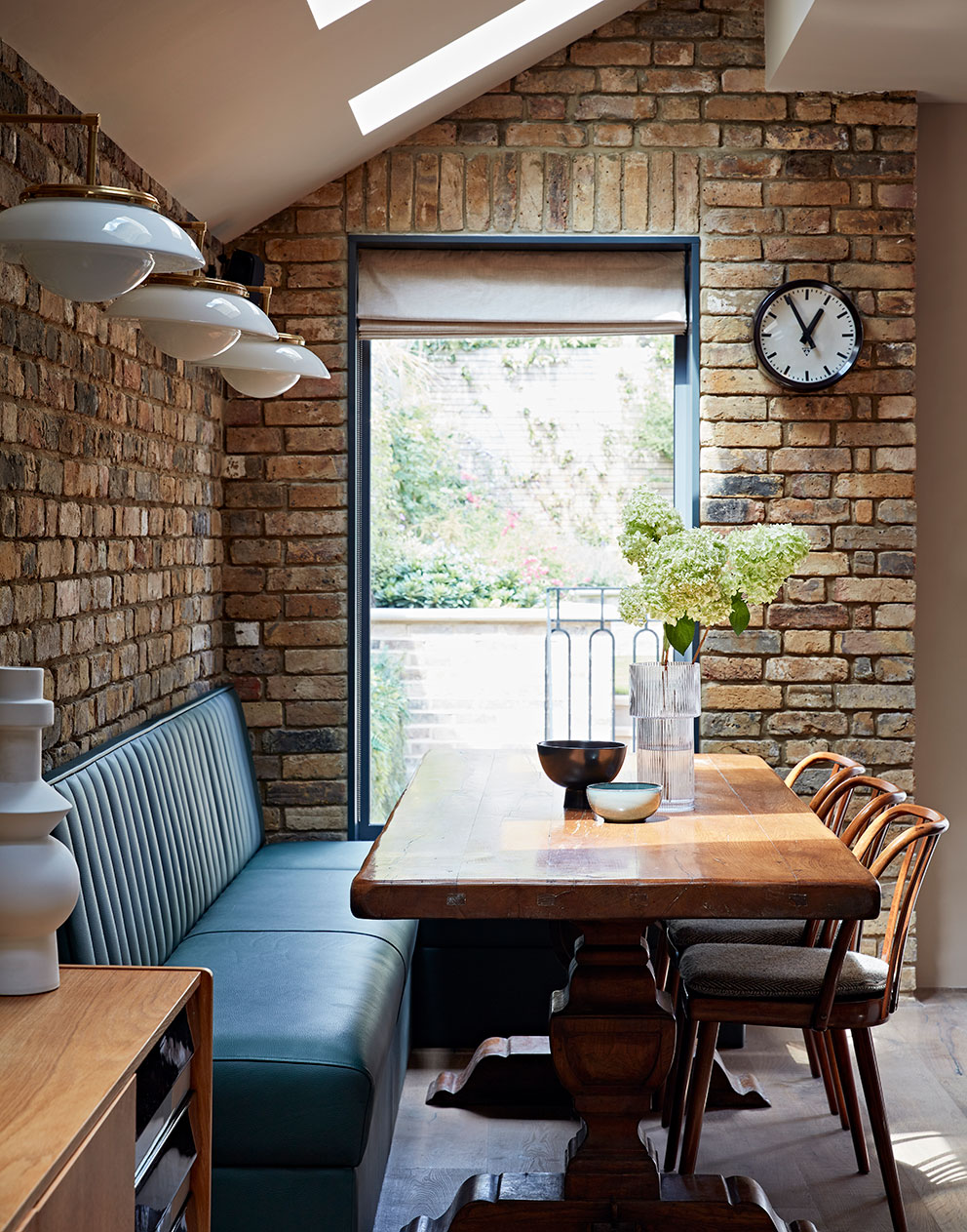 Queens Park dining room with leather banquette and exposed brickworkd