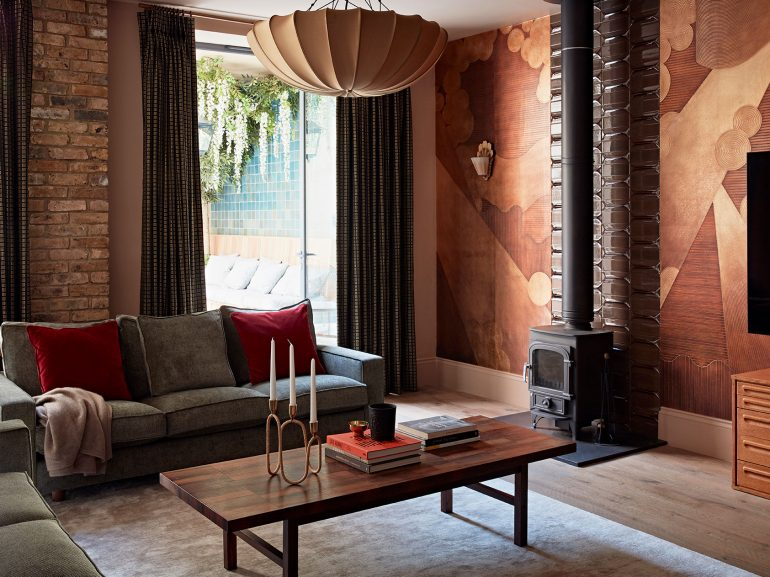 Queens Park sitting room with warm patterned walls and woodburner