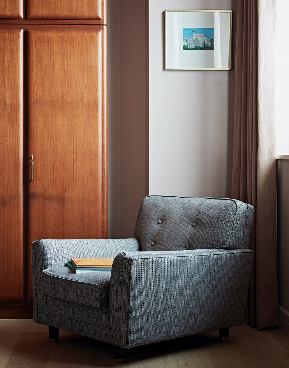West London pied-a-terre upholstered armchair and vintage wooden wardrobe
