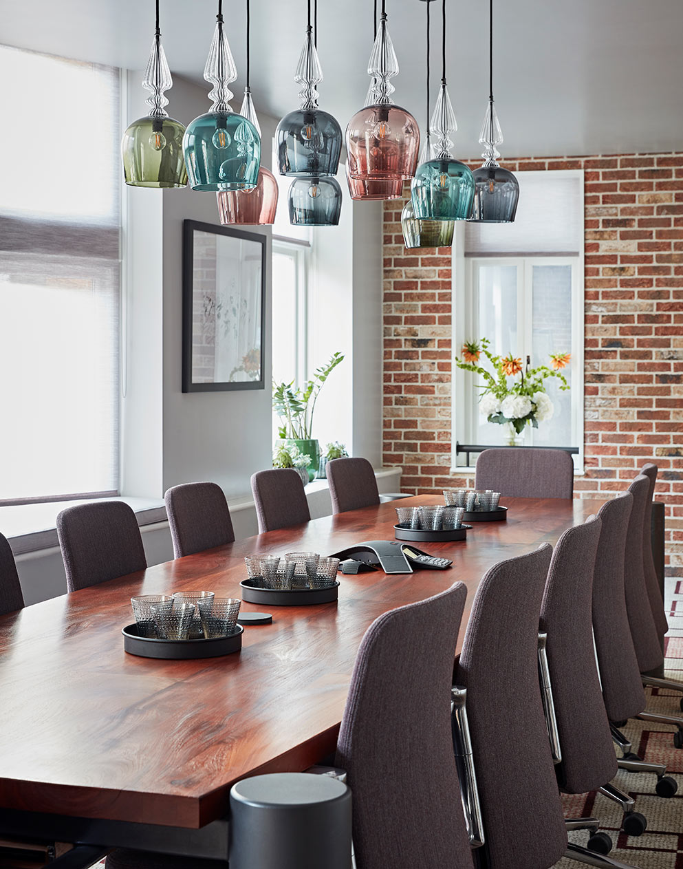 Really Useful Group London HQ meeting room with pastel glass lamps and wooden table