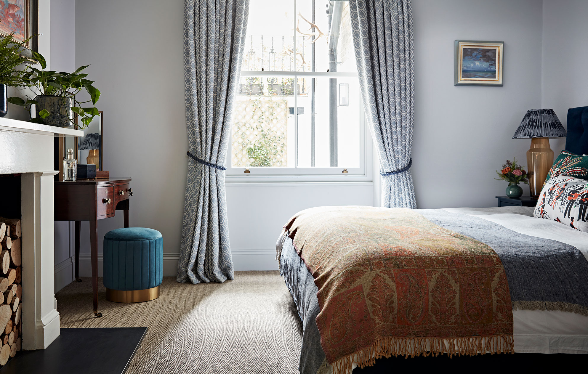 Cosy designer bedroom with unusual throws, grey patterned curtains and dressing table