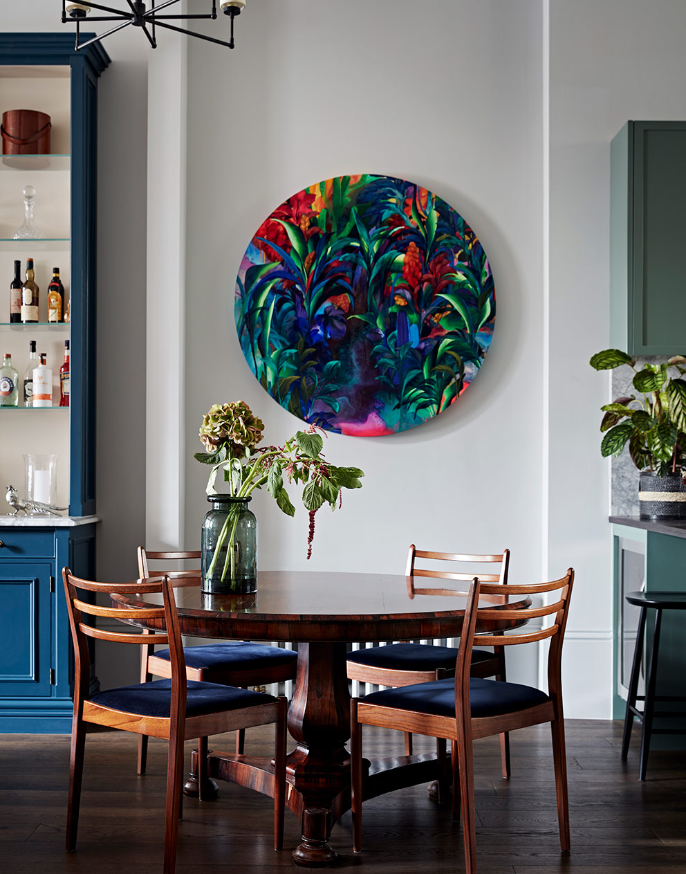 Vintage dining table and chairs with bright circular painting on the wall behind