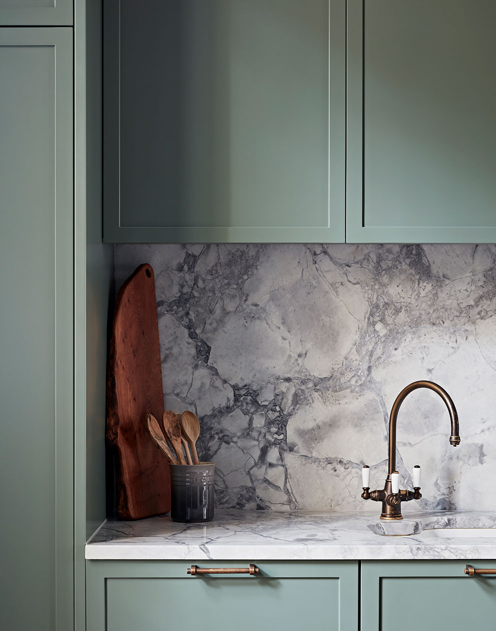 Close up of bespoke kitchen with soft sage green cupboards and light grey marble work surfaces