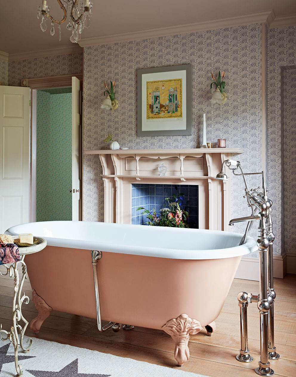 Pink roll top bath standing in centre of bathroom with patterned wallpaper