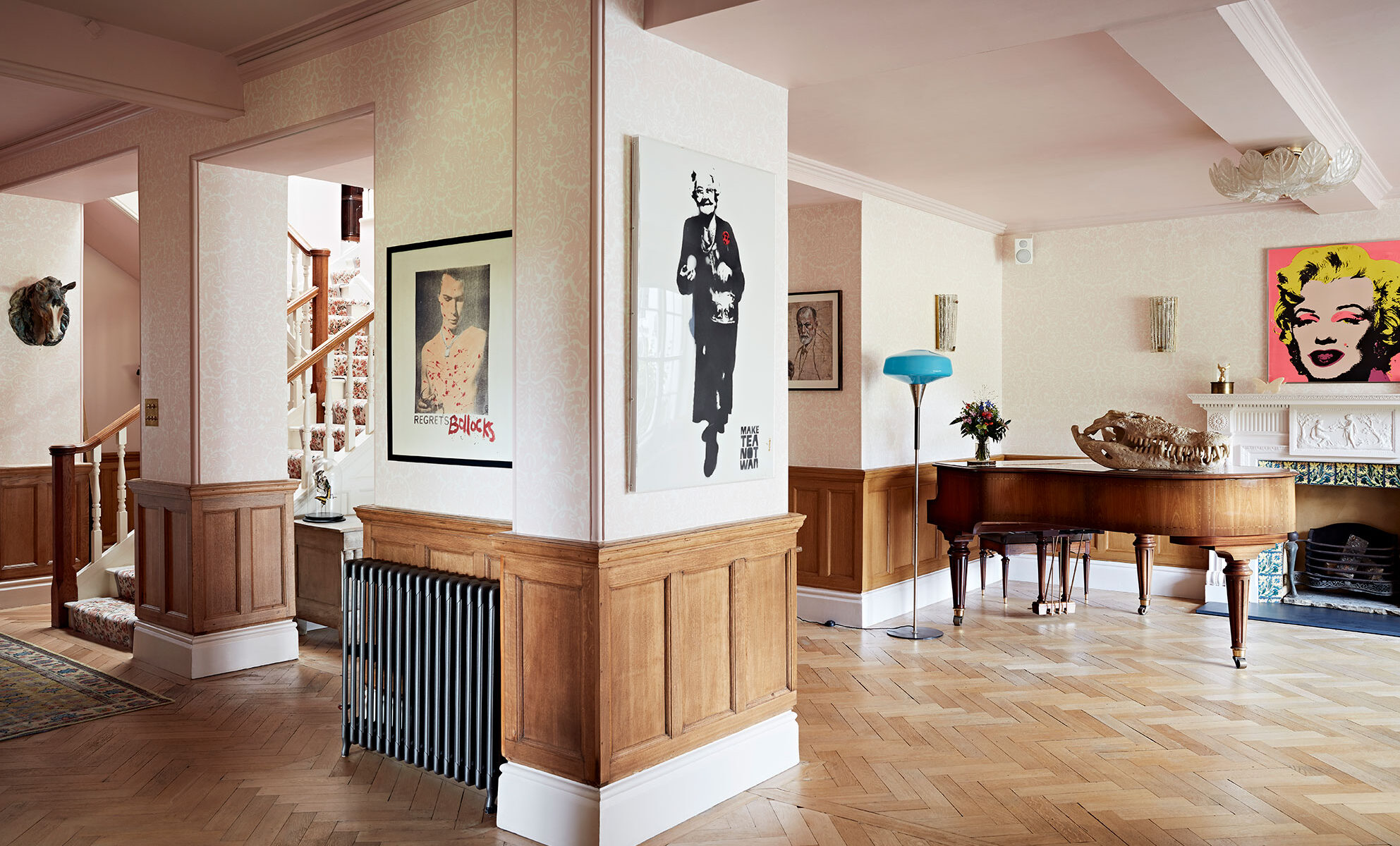 Open plan hallway with herringbone parquet, wood panel walls and a grand piano