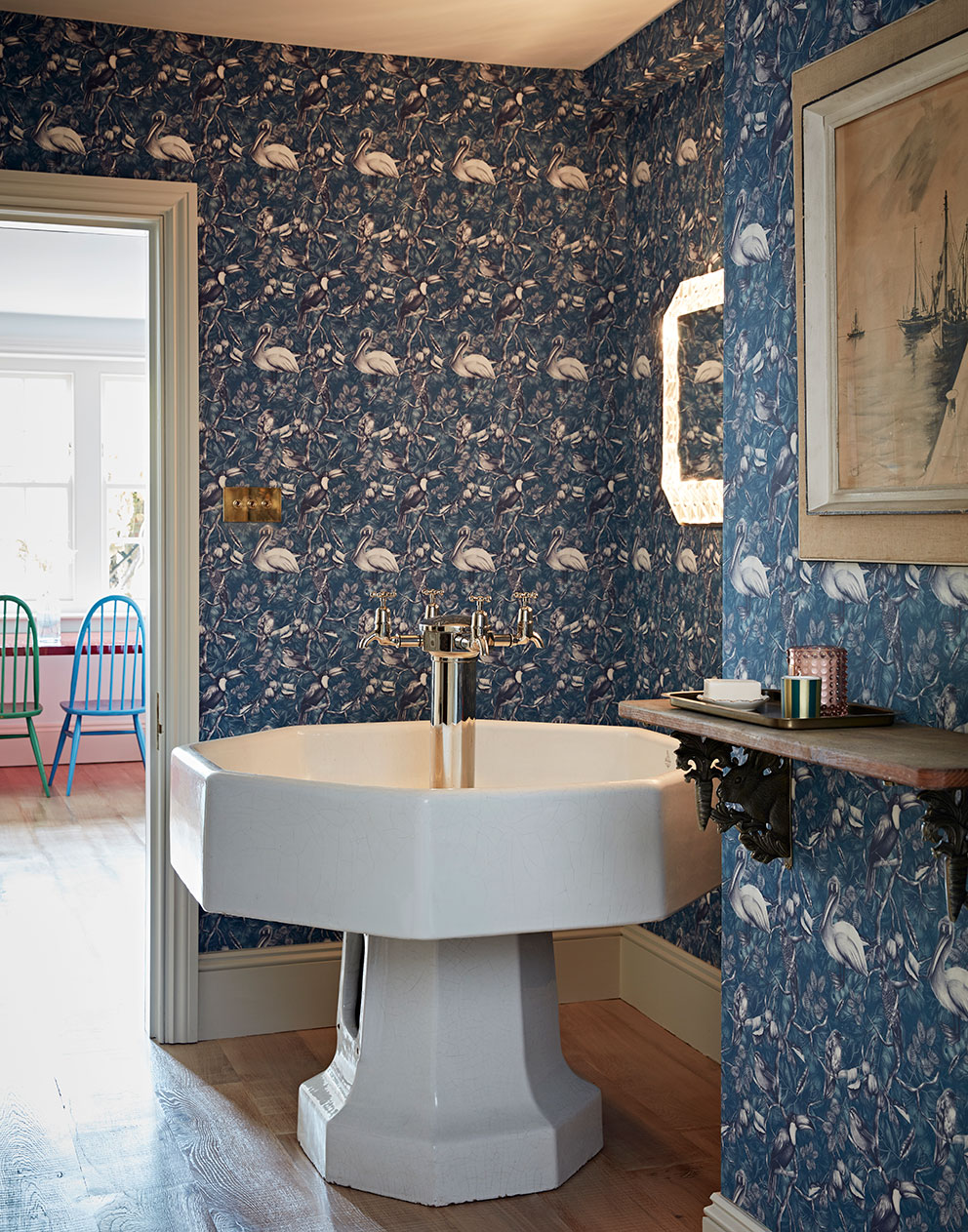 Unusual ceramic drinking fountain in corner of room with blue bird wallpaper