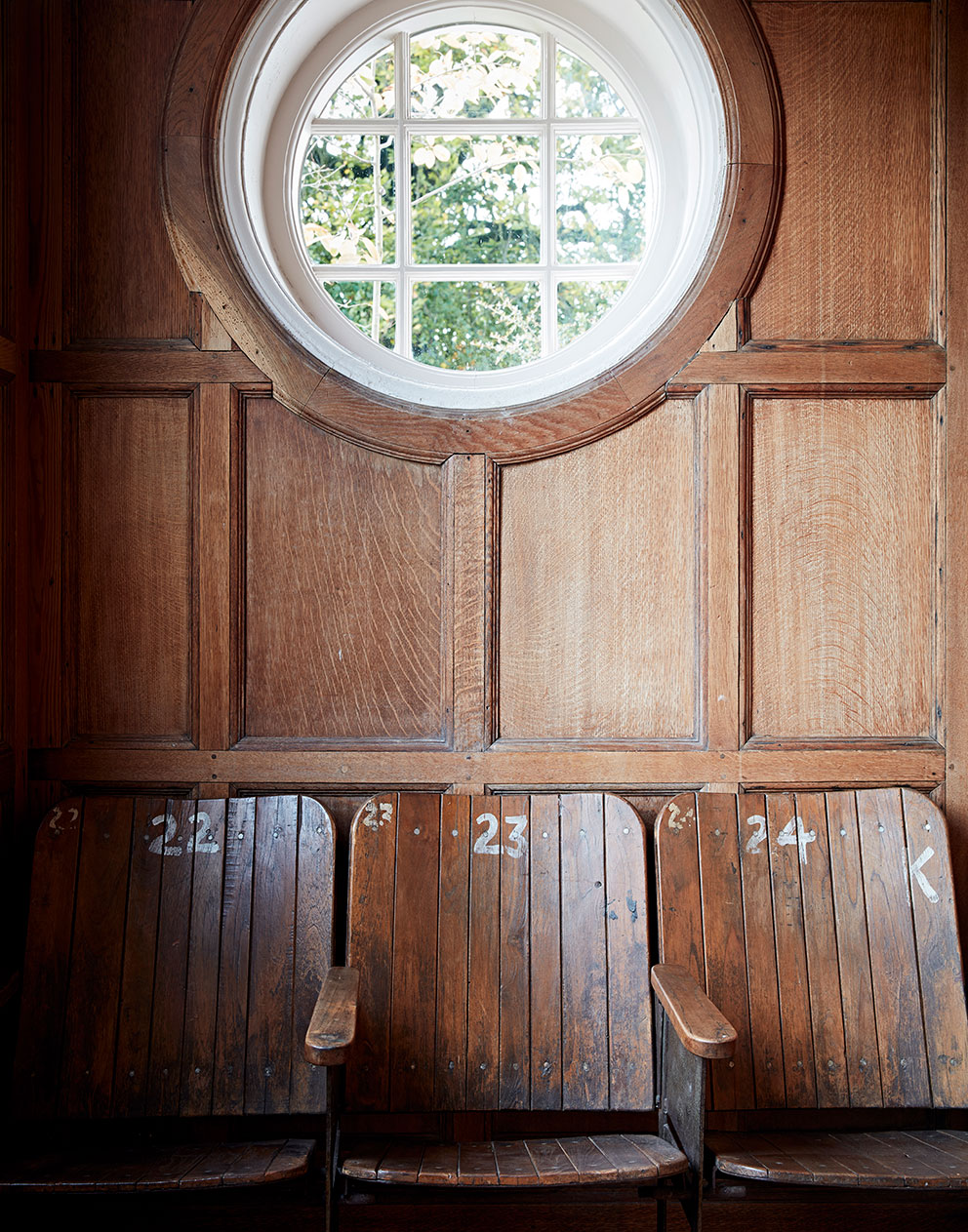 Imaginative interior design showing round window, wood paneling and vintage wooden folding seats